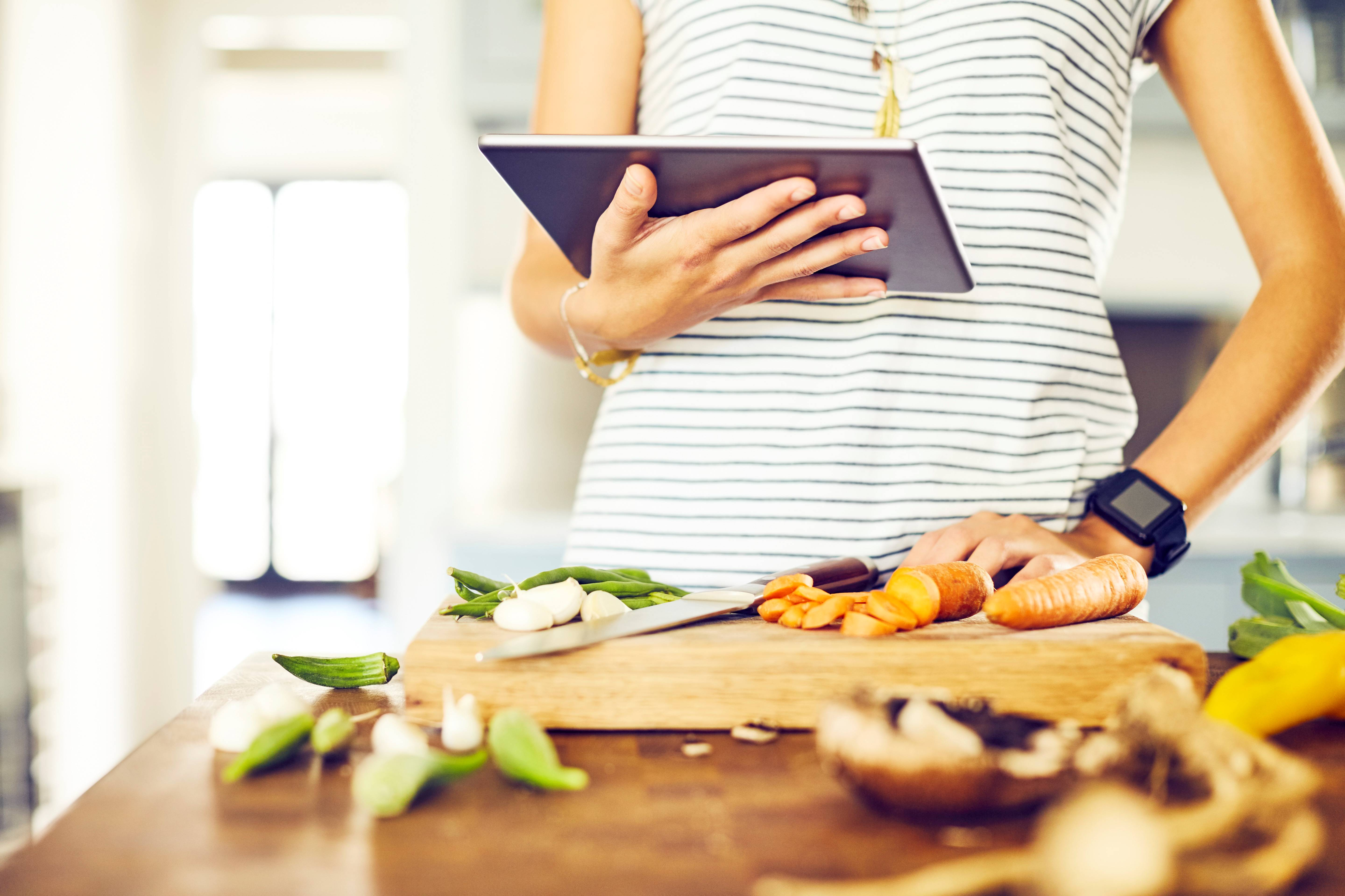 female looking up cooking term on ipad