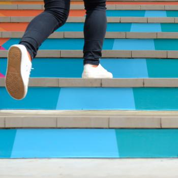 Teenager walking up colorful stairs
