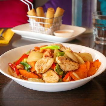A bowl of stir fried chicken and vegetables.