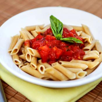 A bowl of whole wheat pasta with sauce on top